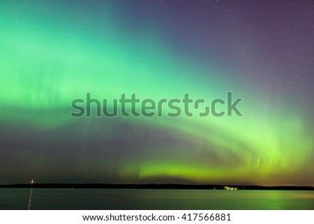 Northern lights over lake in Finland - stock photo
