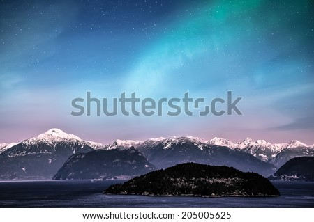 Northern lights over snow capped mountain and lake - stock photo