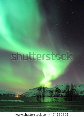 Northern lights over the mountain with reflection near Tromso, northern norway.