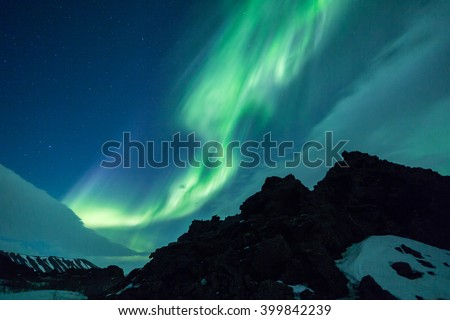 Northern Lights over volcanic rock formations in Iceland landscape - stock photo