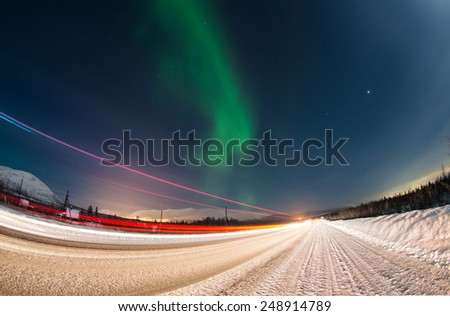 Northern lights over winter road with light trails from moving cars near Apatity town in Murmansk region (Kola peninsula) in northern Russia - long exposure nature background  - stock photo