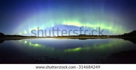 Northern lights panorama with reflection in the lake at night in Finland. Beautiful night sky and mysterious colors above still water.
