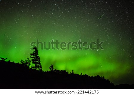 Northern lights with a meteor streaking above. - stock photo