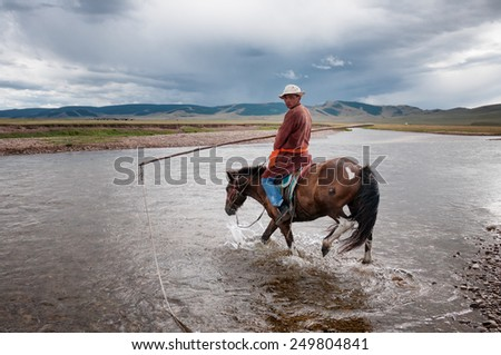 NORTHERN MONGOLIA , MONGOLIA - AUG 06, 2011: Mongolian herder pose fording the river for foreign tourists