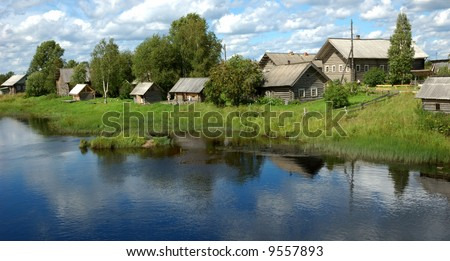 Northern russian village by the river, green grass, blue sky, reflections in water