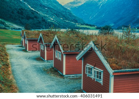 Norway mountains landscape with traditional cabins. Retro style film colors. - stock photo