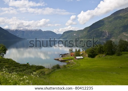 Norway scenery of Sognefjord with fields, houses, garden, mountains - stock photo