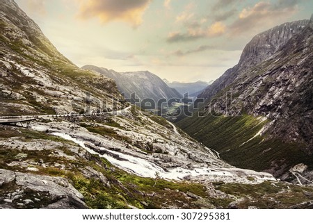"Norway scenic mountain landscape. Famous Norwegian mountain road ""Troll's Path"" (Trollstigen or Trollstigveien). Mountains valley in afternoon with clouds and sunshine.  - stock photo"