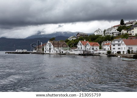 Norwegian fjord in summer, small village in harbour - stock photo
