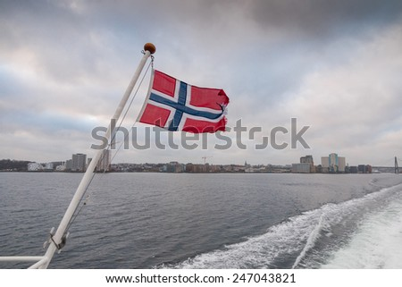 Norwegian flag on a cruise ship, flapping in the cold wind of the Lysefjord with the city of Stavanger in the background - stock photo