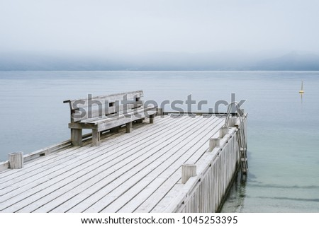 Norwegian landscape in gentle pastel colors. A wooden pier with a rest place. View of the Hardangerfjord Fjord. No far from the city of Oystese