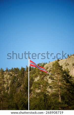 Norwegian pennant on a pole with mountains background - stock photo