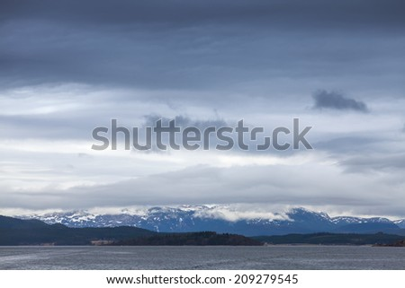 Norwegian sea dark coastal landscape with sea and stormy sky - stock photo