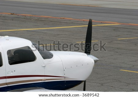 Nose and propeller of a small white plane on the runway