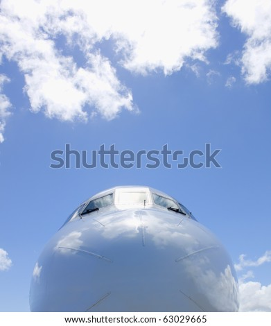 nose of plane with a blue sky and clouds in background