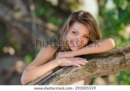 Nostalgic and happy moments of a beautiful girl as she rests behind on a tree trunk - stock photo