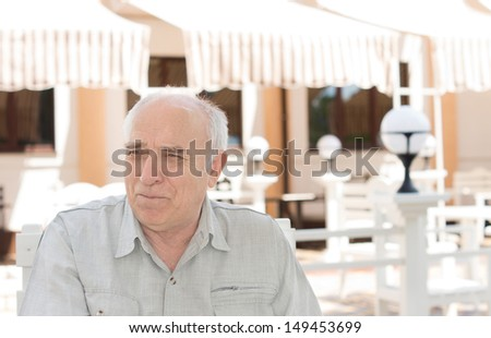Nostalgic Caucasian senior man looking away in front of a house, in a sunny day - stock photo