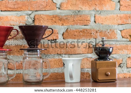 Nostalgic coffee grinder and cup coffee on old table and textured brick wall background