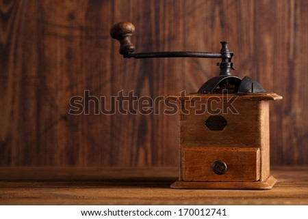 Nostalgic coffee grinder on old table and textured wood background