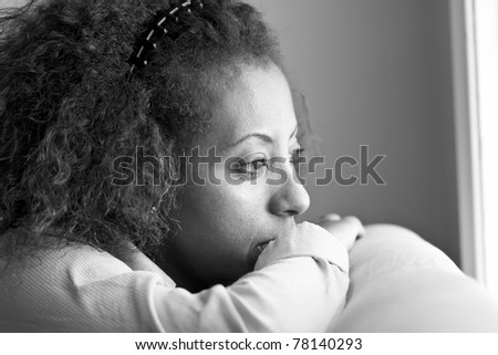 Nostalgic Ethiopian woman looking out the window in deep thought - stock photo