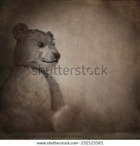 Nostalgic image of an old, well loved bear. Sepia effect with texture and space for text - stock photo