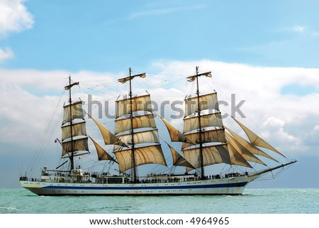 nostalgic sailboat sailing the ocean with cloudy and blue sky background - stock photo