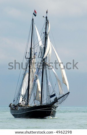 nostalgic sailboat sailing the ocean with cloudy sky background - stock photo