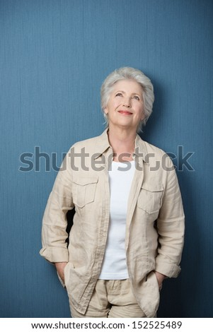 Nostalgic senior Caucasian woman wearing beige Casual shirt and pants and a white T-shirt, standing with her arms in her pockets with a blank chalkboard behind - stock photo