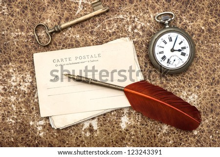 nostalgic vintage background with old post cards, clock, key and feather pen