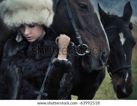Nostalgic young brunette posing next to a horse - stock photo