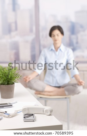 Not answering phone in skyscraper office, female office worker doing yoga meditation in background.? - stock photo