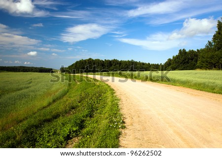 Not asphalted rural road to summertime of year - stock photo