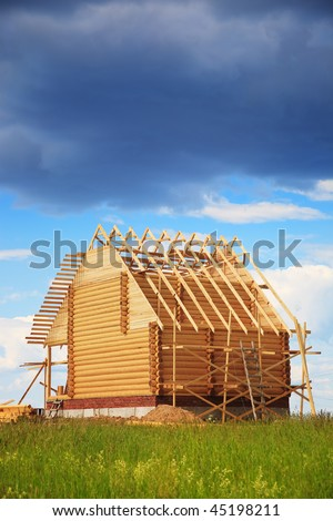 Not completed wooden house under the big dark cloud - stock photo
