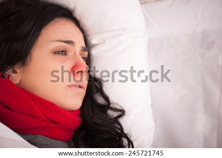 Not feeling too great. Closeup image of young sick woman lying in bed with red nose in thick scarf and looking away in frustration at copy space - stock photo