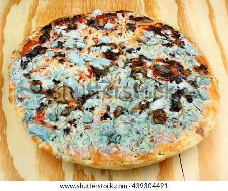 Not fresh, moldy pizza on the wooden table - stock photo