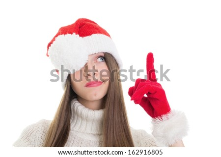 Not impressed pretty Caucasian teenage girl wearing Santa beanie pointing and looking up isolated on white background.