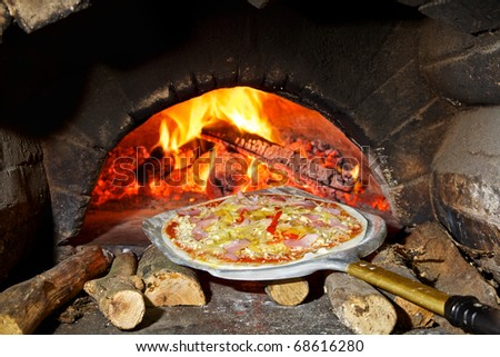 Not prepared pizza with mushrooms on an aluminum shovel in front of the furnace on fire wood