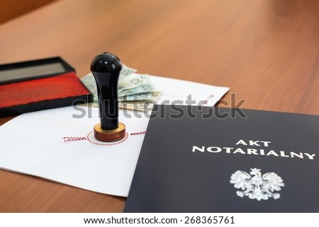 Notarial act signed by the notary and Polish money - stock photo