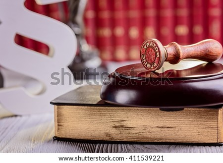 Notary public metal stamper with symbols of law in court library - stock photo