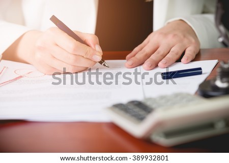 Notary Public signing the contract in her office. Law office - stock photo