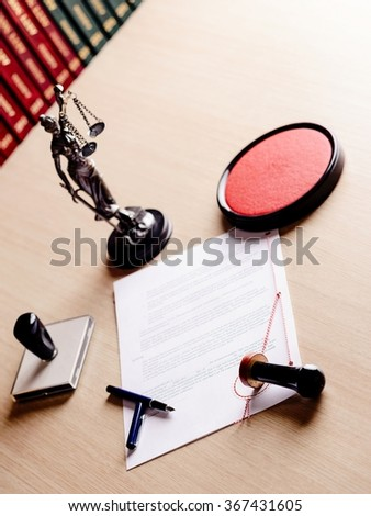 Notary public working tools, his stamp, pen, figurine of goddess of justice Themis and contract waiting for his sign - stock photo
