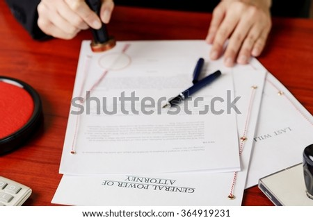 Notary's public hands stamping power of attorney. Notary public accessories - stock photo