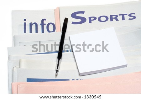 Note and pen, over stacked sports newspapers on white background - stock photo