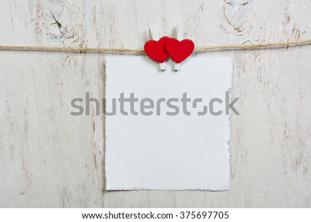 note attached with two red hearts clothespins - stock photo