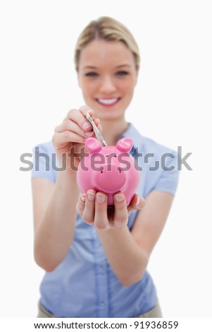 Note being put into piggy bank by woman against a white background