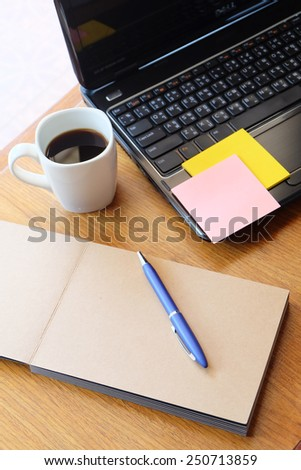 note book and black coffee on wooden table with post it   - stock photo