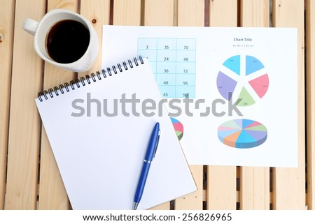 note book and chart on the wooden table with back coffee - stock photo