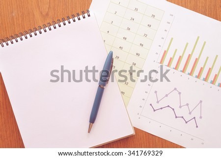 note book and chart on wooden table with vintage style - stock photo