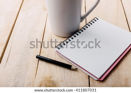 note book and cup on wooden table