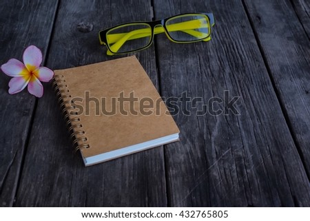Note book and glasses on wooden background, flower. - stock photo
